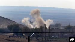 Asap membumbung di atas kota perbatasan strategis Suriah, Kobani, Minggu 5 Oktober 2014.
