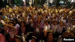 Well-wishers hold lit candles and portraits of Thailand's King Bhumibol Adulyadej at Siriraj hospital, where a group has gathered to mark his 88th birthday, in Bangkok, Thailand, Dec. 5, 2015.