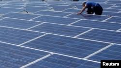 一名工人在日内瓦展览中心的屋顶上安装太阳能电池板