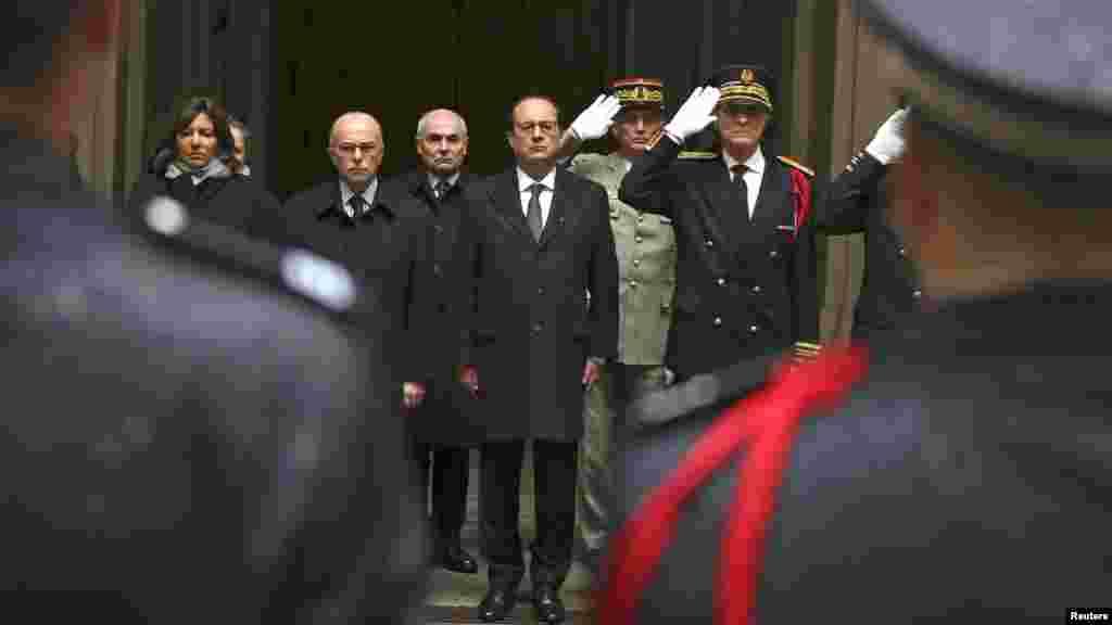 Le président français François Hollande, centre, le ministre de l'Intérieur Bernard Cazeneuve, deuxième à gauche, le maire de Paris Anne Hidalgo, à gauche, et le préfet de police, Bernard Boucault, à droite, observent une minute de silence à la Préfecture de Paris à Paris, le 8 janvier 2015.