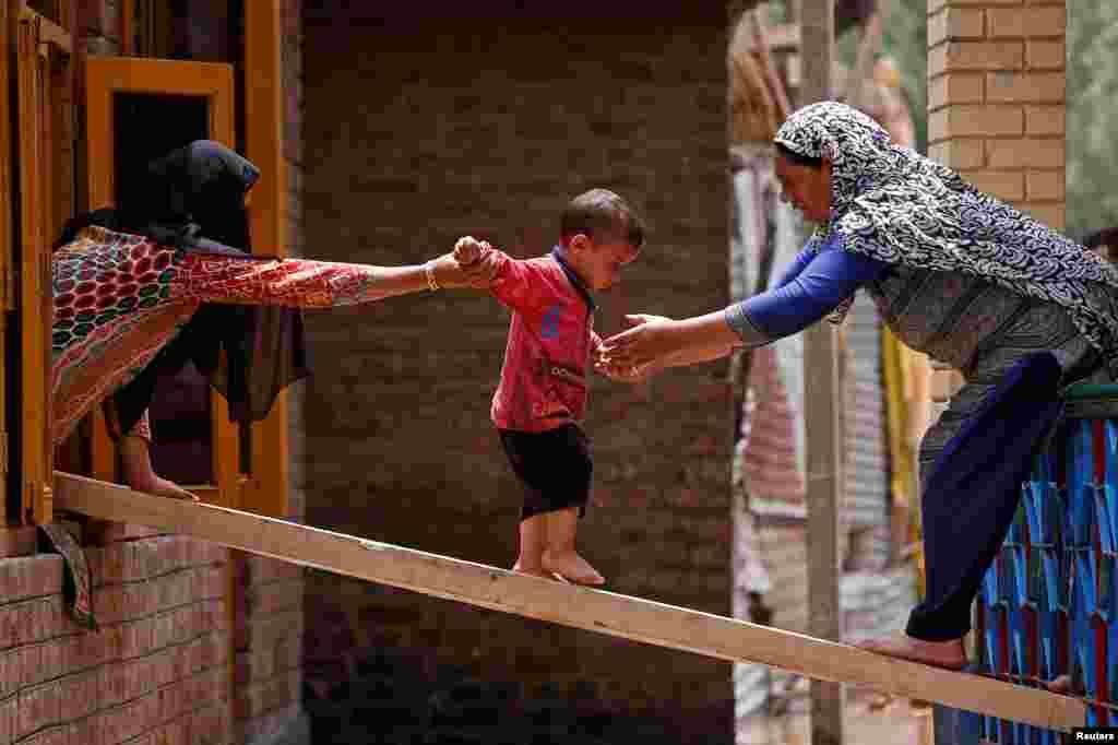 집중 호우로 홍수가 발생한 인도 스리나가르 외곽의 테일벌에서 여성들이 아이가 나무 판자를 건너 다른 집으로 옮겨 가도록 돕고 있다.