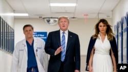 Prezidan Trump (mitan), Premyè Dam Melania Trump ak Doktè Igor Nichiporenko, pandan prezidan an t ap vizite yon lopital nan Florid kote viktim fiziyad vandredi 16 fevriye a t ap resevwa swen.