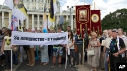 "FILE - Believers take part in a rally in support of the Russian Orthodox Church, in Moscow, Russia, July 22, 2012. Their banner reads ""Jail for blasphemy!"""