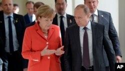 Kanselir Jerman Angela Merkel (kiri) berbicara dengan Presiden Rusia Vladimir Putin menjelang final Piala Dunia di Rio de Janeiro, Brazil (13/7).