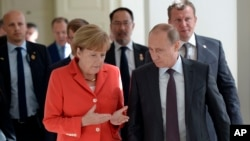 Russian President Vladimir Putin and German Chancellor Angela Merkel speak to each other before the World Cup final between Germany and Argentina in Rio de Janeiro, Brazil.