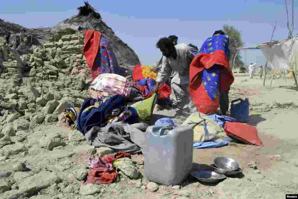 Survivors collect their belongings near the rubble of a mud house after it collapsed following an earthquake in the town of Awaran, southwestern Pakistani province of Baluchistan, Sept. 25, 2013.