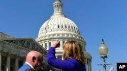 La exlegisladora demócrata por Arizona Gabrielle Giffords acompañada de su esposo el astronauta Mark Kelly levanta el puño hacia el Congreso de EE.UU. mientras pide un control de armas más estricto luego del ataque masivo en un concierto en Las Vegas, Nevada. Oct. 2, 2017.