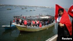 A Palestinian woman holds a Turkish flag as activists ride a boat during a rally ahead of the 4th anniversary of the Mavi Marmara Gaza flotilla incident, at the seaport of Gaza City, May 29, 2014.