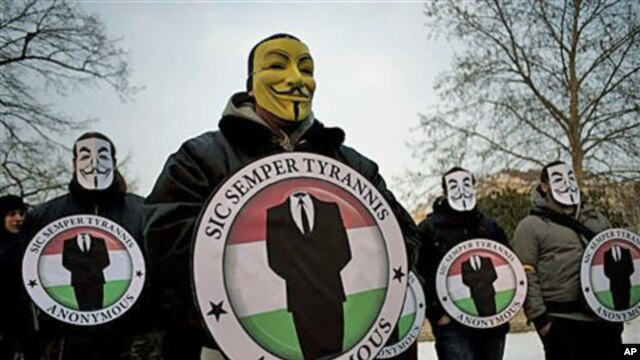Protestors wearing Guy Fawks masks hold the logos of the international hacker group Anonymous during a demonstration against Anti-Counterfeiting Trade Agreement, ACTA, in Budapest, Hungary, February 11, 2012.