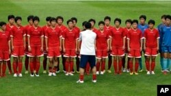 North Korean women's national soccer team players listen to head coach Kim Kwang Min after training session, Seoul World Cup stadium, South Korea, July 19, 2013.
