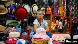 FILE - Souvenirs are offered to tourists visiting the Amphawa floating market at Samut Songkhram province, Thailand. More than 10 percent of the country's 67 million residents are 65 or older.
