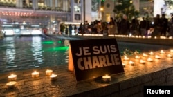 "A placard reading ""I am Charlie"" and candles are placed as a tribute to the victims following a shooting by gunmen at the offices of French weekly newspaper Charlie Hebdo in Paris, during a candlelight vigil at the financial Central district in Hong Kong,"
