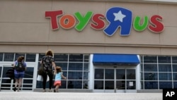 FILE - Shoppers walk into a Toys R Us store, in San Antonio, Texas, Sept. 19, 2017. Toys R Us says it will be closing some U.S. stores and converting others to cobranded locations as it continues to deal with its financial restructuring following its bankruptcy filing.