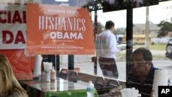 Spanish language election campaign signs promoting President Barack Obama hang on the windows at Lechonera El Barrio Restaurant in Orlando, Florida, October 26, 2012.