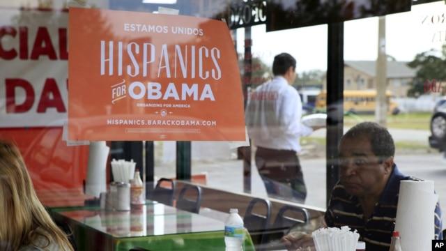 Spanish language election campaign signs promoting President Barack Obama hang on the windows at Lechonera El Barrio Restaurant in Orlando, Florida, October 26, 2012.