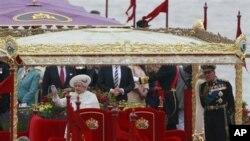 Ratu Elizabeth II dan suaminya, Pangeran Phillip dalam perayaan iring-iringan perahu di sungai Thames, London hari Minggu.