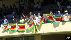 Zimbabweans stand holding flags, during the 36th over of a cricket match between New Zealand and Zimbabwe, at Queens Sports Club in Bulawayo, Zimbabwe, Aug. 6, 2016.