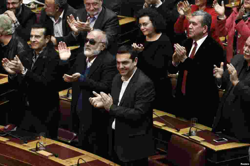 Alexis Tsipras, opposition leader and head of radical leftist Syriza party, and his party's lawmakers applaud after the last round of a presidential vote in Athens, Dec. 29, 2014.