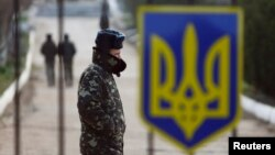A Ukrainian soldier walks near a closed entrance gate at an airforce base in the Crimean town of Belbek March 20, 2014.
