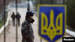一名乌克兰军人从克里米亚城镇贝尔贝克某空军基地被关闭的大门旁走过。(2014年3月20日)