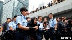 Seorang pengunjuk rasa diseret keluar dari lokasi protes oleh pihak berwenang Hong Kong (11/12). Lokasi di luar gedung pemerintah Hong Kong ini biasanya digunakan sebagai kamp utama para pemrotes pro-Demokrasi.