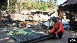 Khaerudin, warga Lombok Utara mengambil sisa bahan bangunan yang masih bisa dipakai dari reruntuhan gempa di Lombok. (Foto ilustrasi: Nurhadi/VOA).