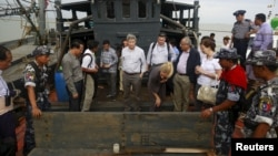 FILE - Myanmar government officials and U.N. officials stand on a boat used for human trafficking at a jetty outside Sittwe, Myanmar.