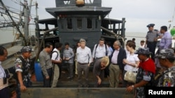Myanmar government officials and U.N. officials stand on a boat used for human trafficking at a jetty outside Sittwe, Myanmar.
