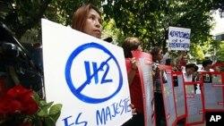 """ປະຊາຊົນໄທທໍາການປະທ້ວງຕໍ່ຕ້ານການຈັບກຸມອາຈານສອນມະຫາວິທະຍາໄລຄົນນຶ່ງ ໃນຂໍ້ຫາໝີ່ນປະໝາດ ພະມະຫາກະສັດ ຫລື """"lese majeste"""" ຢູ່ສະຖານີຕໍາຫລວດແຫ່ງນຶ່ງໃນບາງກອກ, ວັນທີ 11 ພຶດສະພາ 2011. REUTERS/Chaiwat Subprasom"""