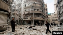 Men inspect the damage at a site hit by what activists said were two barrel bombs dropped by forces loyal to Syria's President Bashar al-Assad in Aleppo's al-Shaar neighborhood Feb. 26, 2015.