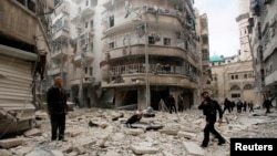 FILE - Men inspect the damage at a site hit by what activists said were two barrel bombs dropped by forces loyal to Syria's President Bashar al-Assad in Aleppo's al-Shaar neighborhood, February 26, 2015.