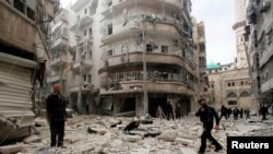 FILE -- Men inspect damage at site of barrel bomb attack by forces loyal to Syria's President Bashar al-Assad, al-Shaar neighborhood, Aleppo, February 26, 2015.
