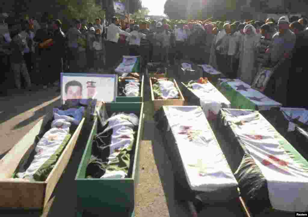 Syrian residents gather in front of the bodies of people, whom protesters say were killed by forces loyal to Syria's President Bashar al-Assad, during their funeral in Dara'a June 9, 2012.