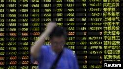 2015年8月24日,一名投資者站在股票信息電子屏前。當天,上證指數暴跌8.5%。 (資料照片)