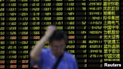 Investor berdiri di depan papan elektronik berisi informasi saham di sebuah pialang saham di Shanghai, China (24/8). (Reuters/Aly Song)