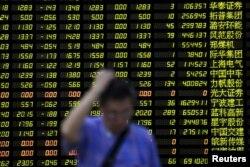 Nhà đầu tư đứng trước bảng điện tử hiển thị thông tin chứng khoán ở Trung Quốc.