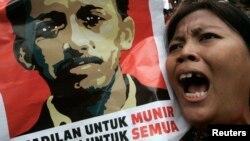 Seorang demonstran meneriakkan slogan sambil membawa poster Munir Said Thalib dalam sebuah protes di luar kantor Badan Intelijen Nasional (BIN), Jakarta. (Foto: Dok)