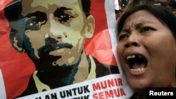 In this undated file photo, a protester holds a poster of Munir Said Thalib during a demonstration outside the National Intelligence Agency (BIN) office in Jakarta.