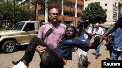 Un journaliste portant une femme blessée
