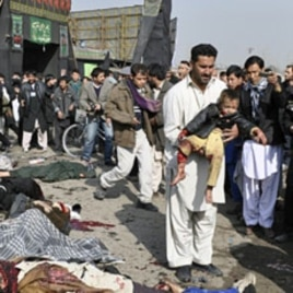 A man carries a wounded boy after a suicide blast targeting a Shi'ite Muslim gathering in Kabul, December 6, 2011