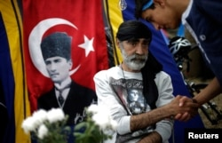 Protesters greet each other near a portrait of Mustafa Kemal Ataturk, founder of modern Turkey, at Gezi Park near Taksim Square in Istanbul, June 6, 2013.
