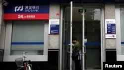 一名女士打开上海浦东发展银行开设在北京的一所支行的大门。(2011年7月6日)