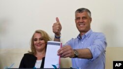 Kosovo's prime minister Hashim Thaci, joined by his wife, Lumnije, casts his ballot at a polling station in the Kosovo capital of Pristina Sunday, June 8, 2014.