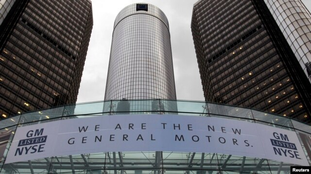 FILE - A banner hangs at the front of the General Motors Co world headquarters  in Detroit, Michigan.