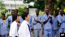 Elementos dos Caminhos de Ferro Chineses envolvidos na construção de uma estrada em Kinshasa, recebidos por trabalhadores congoleses
