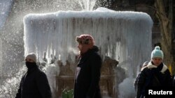 People walk past an ice covered Josephine Shaw Lowell Memorial Fountain, in frigid temperatures in Bryant Park in the Manhattan borough of New York City, Jan. 8, 2015.