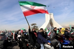 Seorang perempuan Iran melambaikan bendera kebangsaannya saat mengikuti pawai kendaraan bermotor dalam perayaan HUT ke-42 revolusi Islam di Teheran, Iran, 10 Februari 2021. (Majid Asgaripour/WANA via REUTERS)