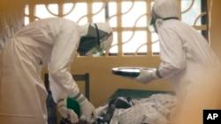 Bác sỹ Kent Brantly (trái) chữa trị cho một bệnh nhân nhiễm virus Ebola ở Liberia.