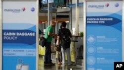 Travelers check in at a Malaysia Airlines counter at Kuala Lumpur International Airport in Sepang, Malaysia, July 18, 2014.
