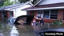 FILE - Andrew Saldivar, left, removes a car battery given to him by a neighbor, which he later installed on a boat to save Houstonians still stranded by the floods. (Photo courtesy of Andrew Saldivar)